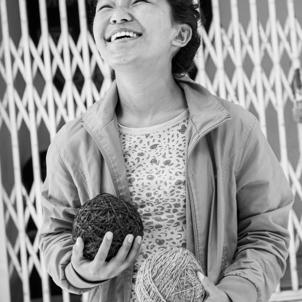 Happy woman holding two balls of yarn