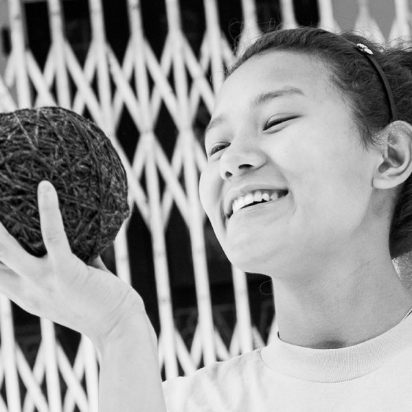 Close-up of a woman holding up a ball of yarn and smiling